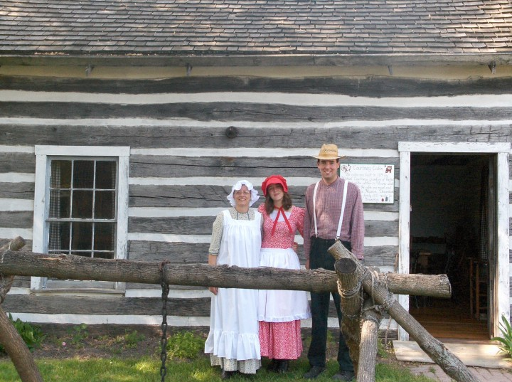 Pioneer family stands in front of a log cabin