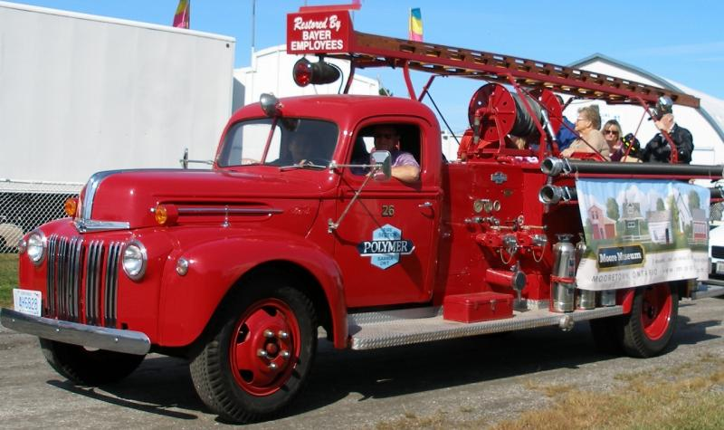 photo of red fire truck with people riding in Brigden Fair parade